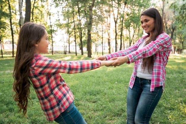 Lächelnde mutter und tochter, die im park spielen Kostenlose Fotos