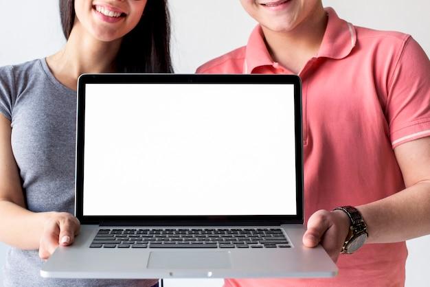 Lächelnde paare, die den laptop zeigt leeren weißen schirm halten Kostenlose Fotos