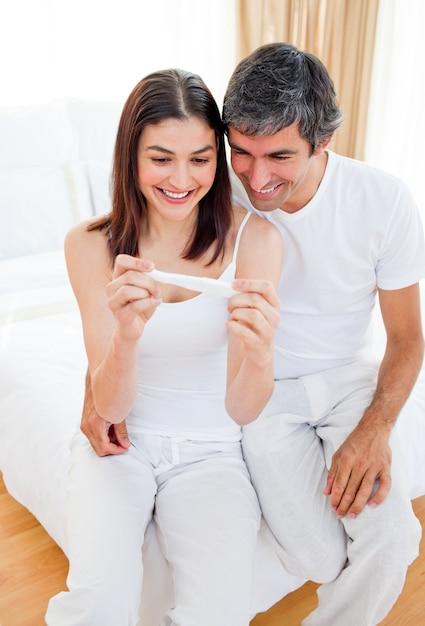 Lächelnde paare, die ergebnisse eines schwangerschaftstests herausfinden Premium Fotos