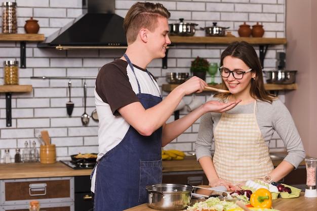 Lächelnde paare, die lebensmittel beim zusammen kochen schmecken Kostenlose Fotos