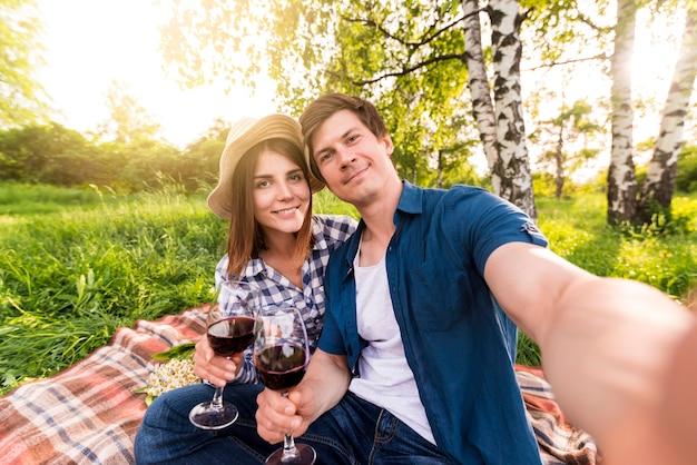 Lächelnde paare, die selfie auf picknick nehmen Kostenlose Fotos