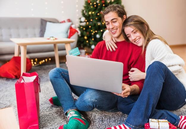 Lächelnde paare mit laptop auf fußboden Kostenlose Fotos