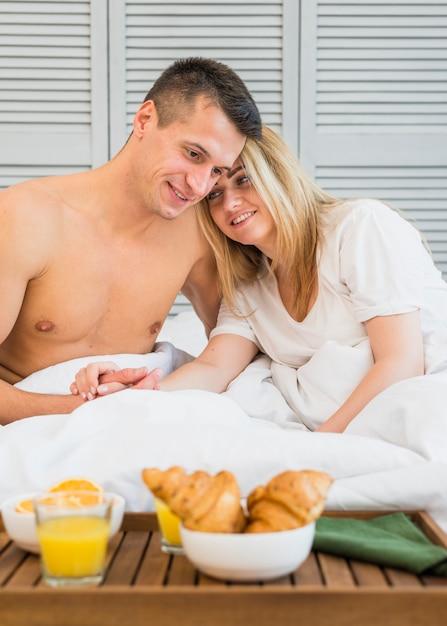 Lächelnde paarhändchenhalten im bett nahe frühstück an