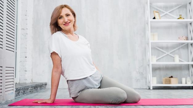 Lächelnde passende ältere frau, die auf der yogamatte betrachtet kamera sitzt Kostenlose Fotos