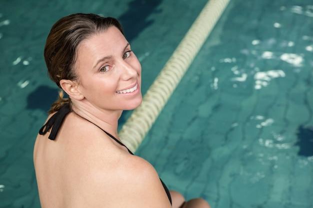 Lächelnde pregant frau, die am rand des pools sitzt und zurück der kamera betrachtet Premium Fotos