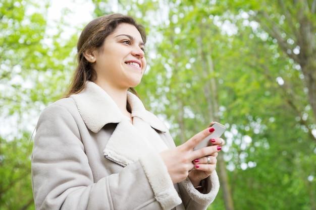 Lächelnde recht junge frau, die smartphone im park verwendet Kostenlose Fotos