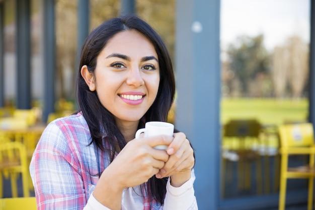 Lächelnde recht junge frau, die trinkenden kaffee im café genießt Kostenlose Fotos