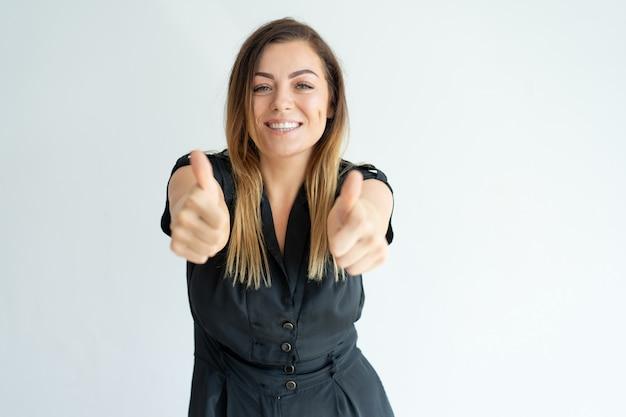 Lächelnde recht junge frau im schwarzen kleid, das thumbs-up beim ausdrücken ihrer zustimmung zeigt Kostenlose Fotos