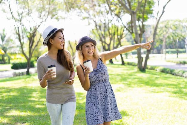 Lächelnde recht junge freundinnen, die in sommerpark gehen Kostenlose Fotos