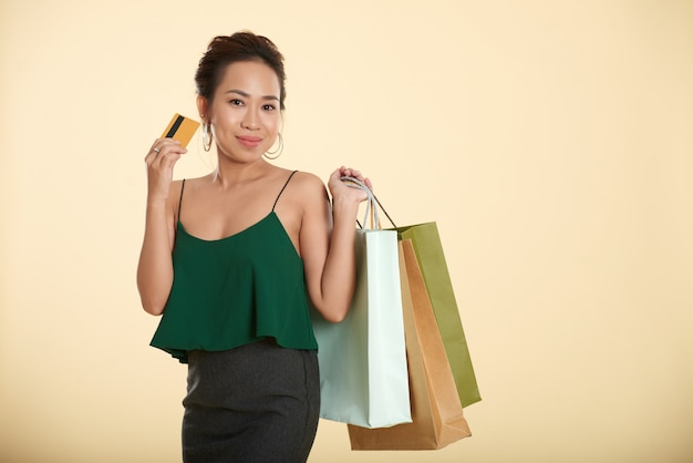 Lächelnde schicke asiatin, die mit einkaufstaschen und kreditkarte aufwirft Kostenlose Fotos