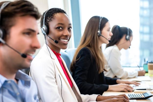 Lächelnde schöne afroamerikanerfrau, die im kundenkontaktcenter mit verschiedenem team arbeitet Premium Fotos