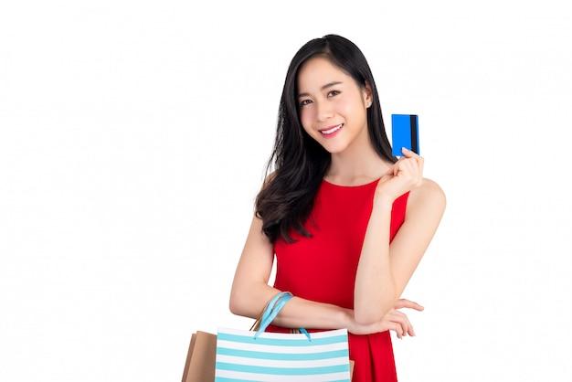 Lächelnde schöne asiatin der junge, die in der hand kreditkarte darstellt Premium Fotos