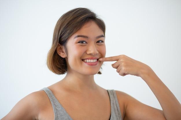 Lächelnde schöne asiatin, die auf ihre zähne zeigt Kostenlose Fotos
