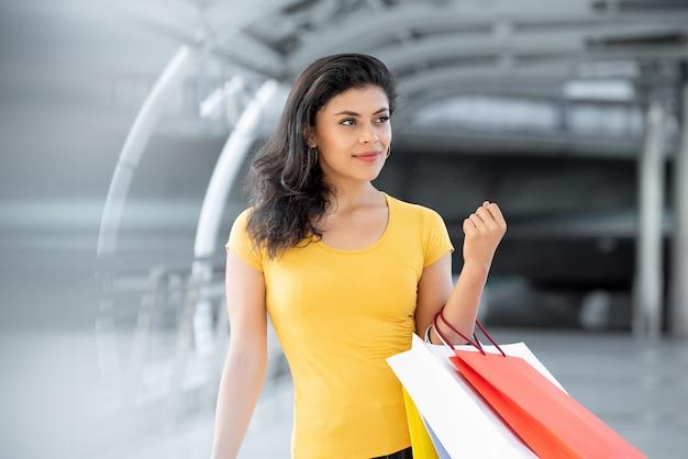 Lächelnde schöne frau, die bunte einkaufenbeutel trägt Premium Fotos