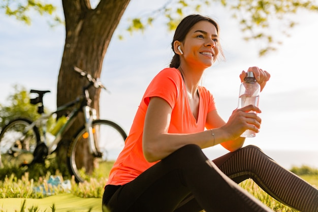 Lächelnde schöne frau, die wasser in der flasche trinkt, die sport am morgen im park tut Kostenlose Fotos