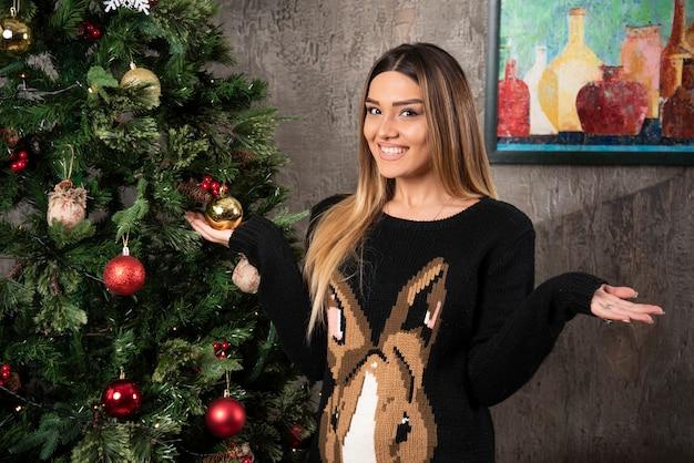 Lächelnde schöne frau im warmen pullover, der mit händen nahe weihnachtsbaum aufwirft. hochwertiges foto Kostenlose Fotos