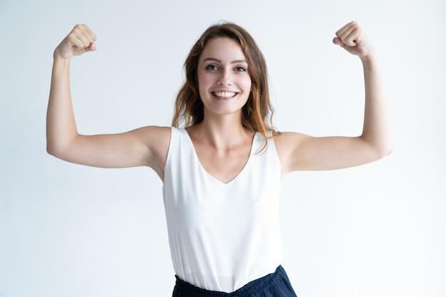 Lächelnde schöne junge frau, die geballte hände anhebt Kostenlose Fotos