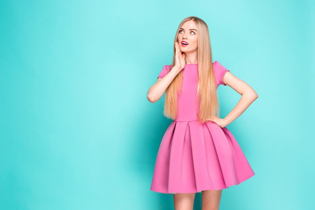 Lächelnde schöne junge frau im rosa minikleid posiert, präsentiert etwas und schaut weg. Kostenlose Fotos