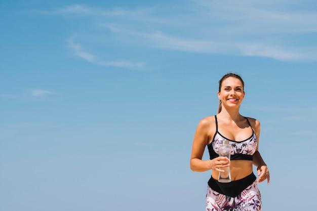 Lächelnde schöne junge frau, welche in der hand die wasserflasche gegen blauen himmel läuft Kostenlose Fotos