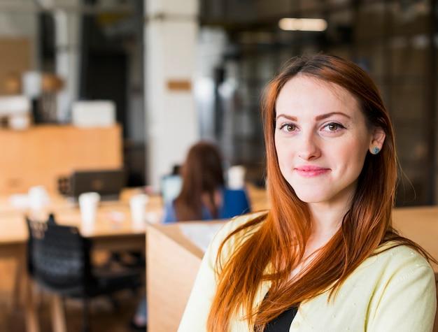 Lächelnde schöne kaukasische frau im büro, das kamera betrachtet Kostenlose Fotos