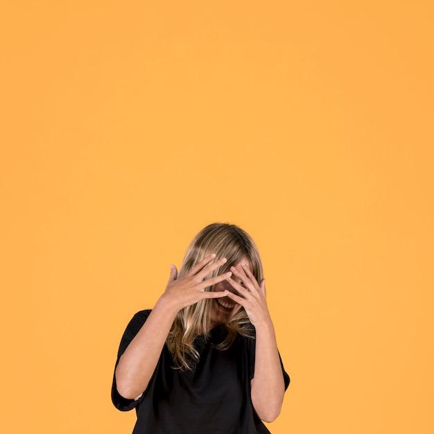 Lächelnde schüchterne frau, die ihr gesicht mit dem finger bedeckt Kostenlose Fotos