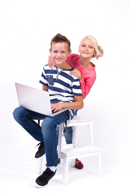 Lächelnde schulkinder lernen mit laptop Premium Fotos