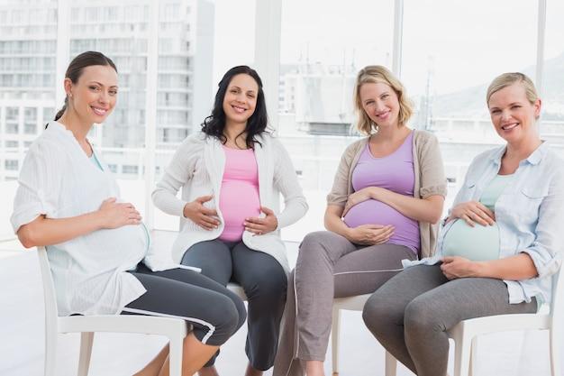 Lächelnde schwangere frauen, die zusammen an der vor der geburt liegenden klasse sitzen Premium Fotos