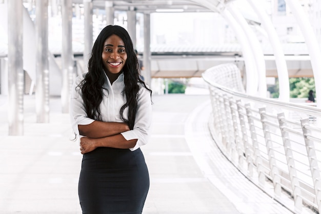 Lächelnde schwarze geschäftsfrau mit den armen gekreuzt Premium Fotos