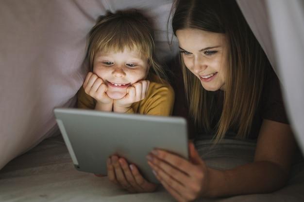 Lächelnde schwestern, die film unter decke aufpassen Kostenlose Fotos