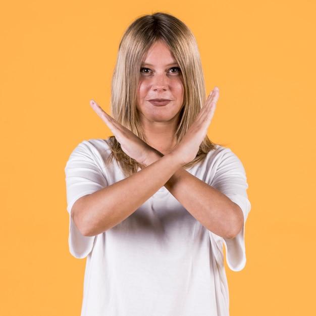 Lächelnde sperrungsfrau, die warnende geste in der gebärdensprache gegen gelben hintergrund zeigt Kostenlose Fotos