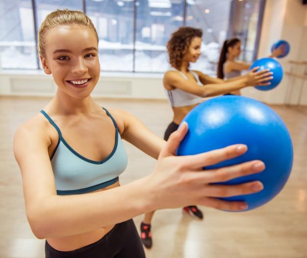 Lächelnde sportmädchen beim ausarbeiten mit eignungsball. Premium Fotos