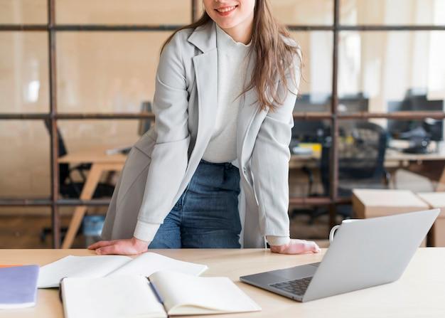 Lächelnde stilvolle geschäftsfrau, die vor laptop steht Kostenlose Fotos