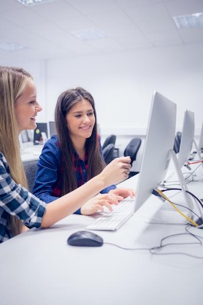 Lächelnde studenten, die an computer an der universität arbeiten Premium Fotos