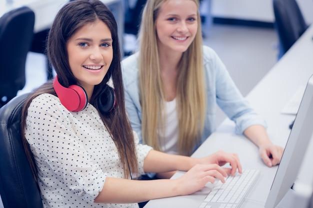 Lächelnde studenten, die computer an der universität verwenden Premium Fotos