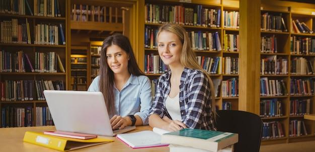 Lächelnde studenten, die laptop in der bibliothek verwenden Premium Fotos