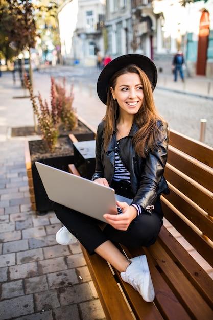Lächelnde studentin geschäftsfrau sitzen auf holzbank in der stadt im park im herbsttag Kostenlose Fotos