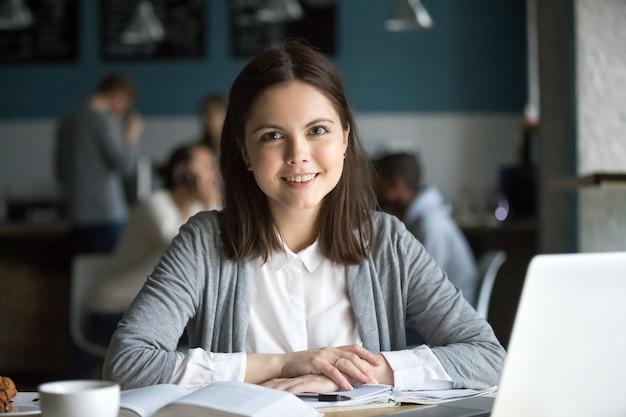Lächelnde studentin, welche die kamera sitzt am cafétisch betrachtet Kostenlose Fotos