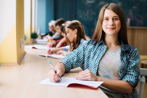 Lächelnde teenager am schreibtisch Kostenlose Fotos