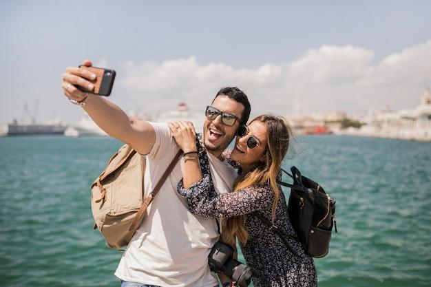 Lächelnde touristische junge paare, die selbstporträt am handy nahe dem meer machen Kostenlose Fotos