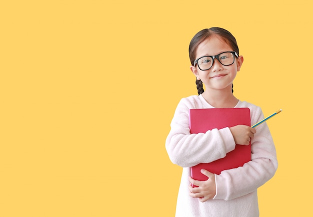 Lächelnde tragende brillenumarmung des schulmädchens ein buch und bleistift in der hand halten lokalisiert über gelb. Premium Fotos