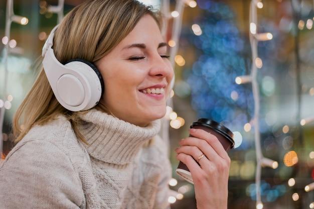 Lächelnde tragende kopfhörer der frau, die schalenweihnachtslichter halten Kostenlose Fotos
