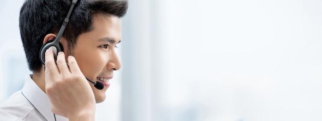 Lächelnde tragende kopfhörer des hübschen asiatischen mannes, die in call-center als kundendienstbetreiber arbeiten Premium Fotos