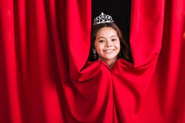 Lächelnde tragende krone des hübschen mädchens, die vom roten vorhang späht Kostenlose Fotos