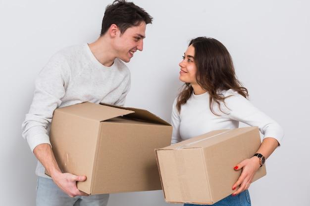 Lächelnde tragende pappschachteln der jungen paare in der hand, die einander gegen weißen hintergrund betrachten Kostenlose Fotos