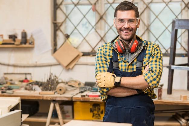 Lächelnde tragende sicherheitsgläser des männlichen tischlers, die vor werkbank mit seinem arm gekreuzt stehen Kostenlose Fotos