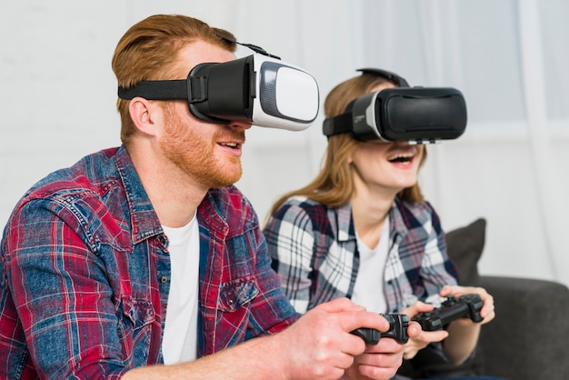 Lächelnde tragende wirklichkeitsbrillen der jungen paare, die das videospiel spielend genießen Kostenlose Fotos