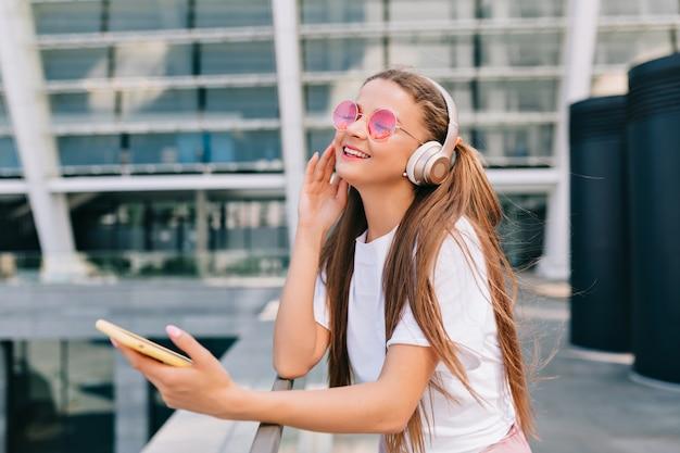 Lächelnde und tanzende junge frau, die ein smartphone hält und musik in kopfhörern hört Kostenlose Fotos