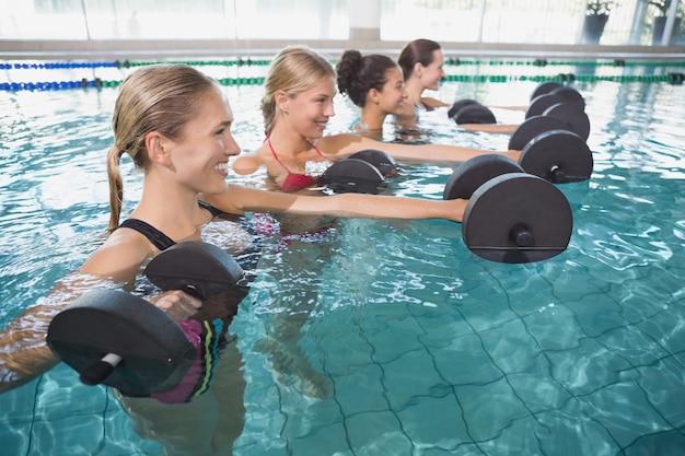 Lächelnde weibliche eignungsklasse, die aquaaerobic mit schaumdummköpfen tut Premium Fotos