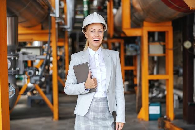 Lächelnde weibliche geschäftsführerin in formeller kleidung, mit schutzhelm auf kopf, der tablette hält und im heizwerk steht. Premium Fotos