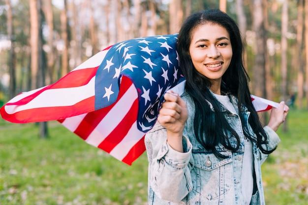 Lächelnde weibliche holding der junge, die usa-flagge fliegt Kostenlose Fotos